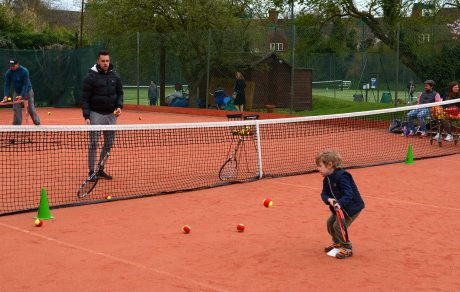 Child being coached on clay court